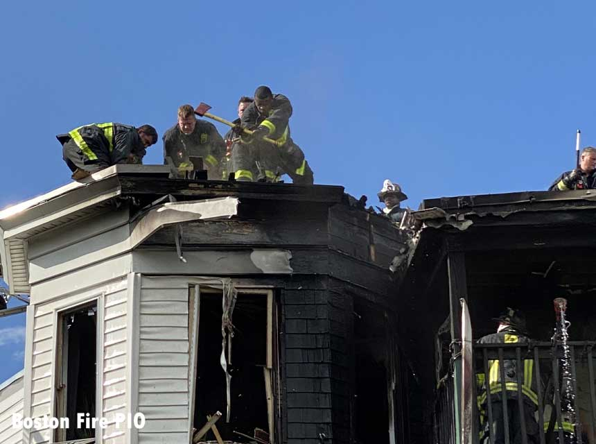 Boston firefighters work on the roof of the burned building
