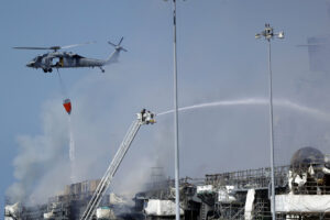 Helicopter dropping water and tower ladder with elevated stream