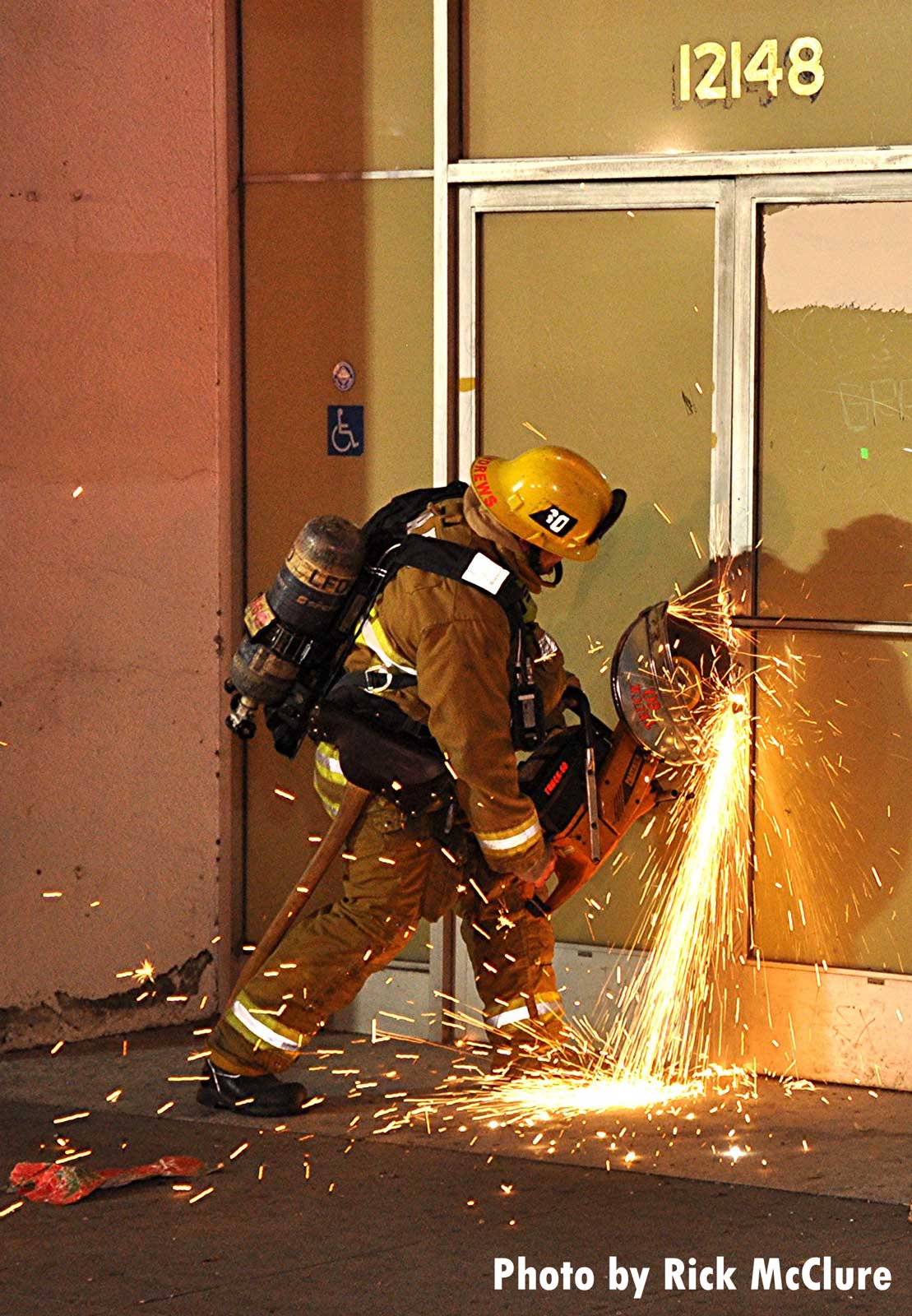 LAFD firefighter using a power saw to cut through a door