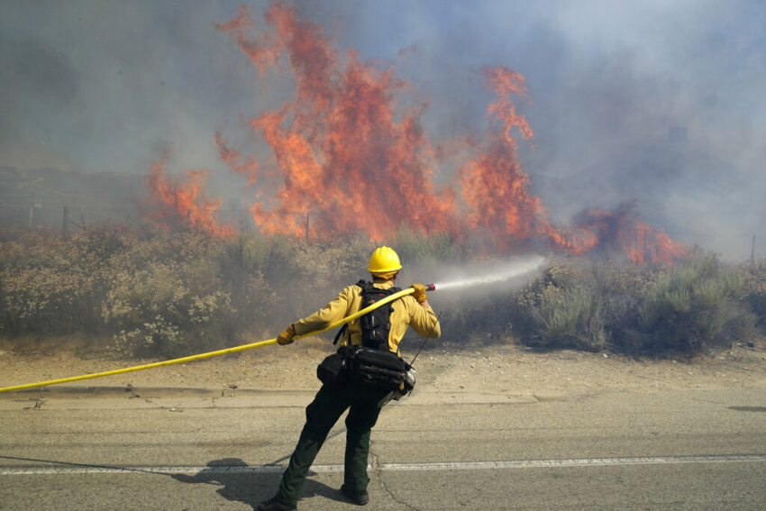 Firefighter with a line flowing water on wildfire in California