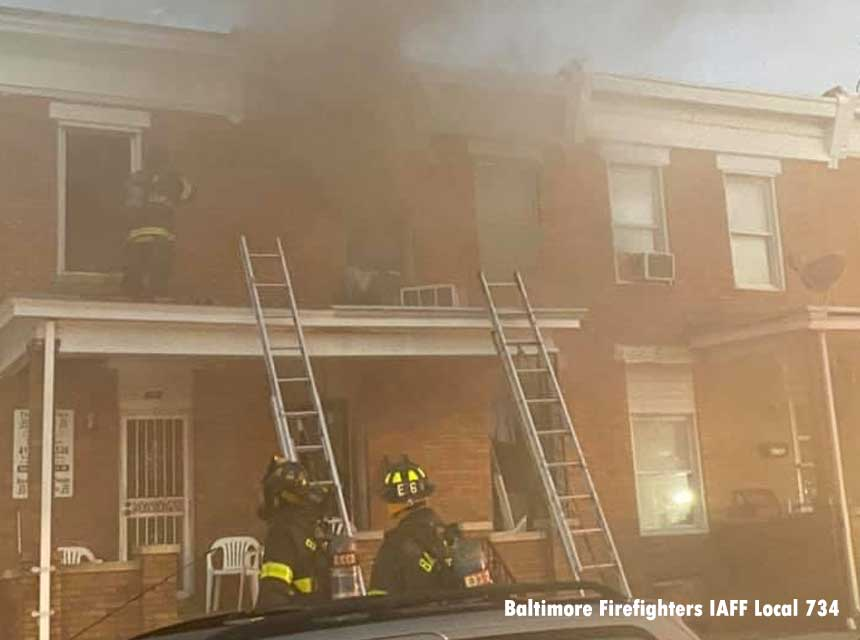 Firefighters with ground ladders at row home fire