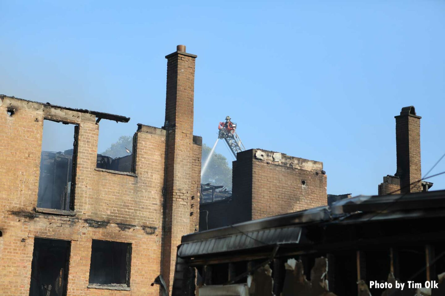 Firefighter on a ladder behind burned out buildings