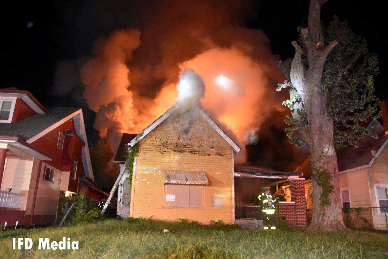 Flames and smoke rise from an intentionally set fire in Indianapolis as crews work