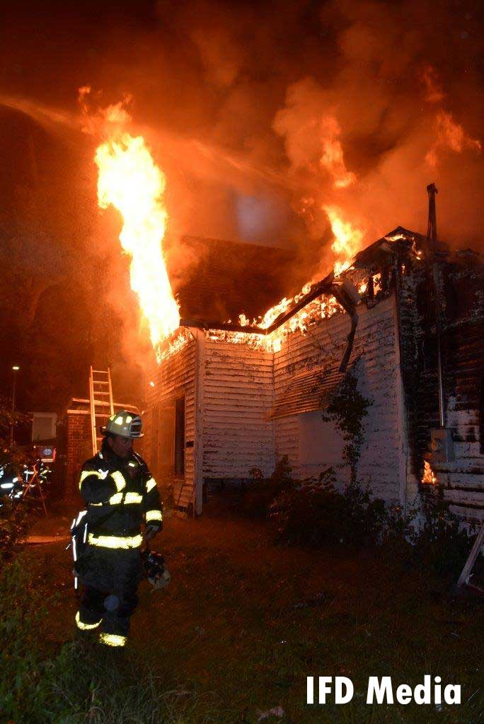 Firefighter at the scene of an arson fire as flames shoot from underneath a roof