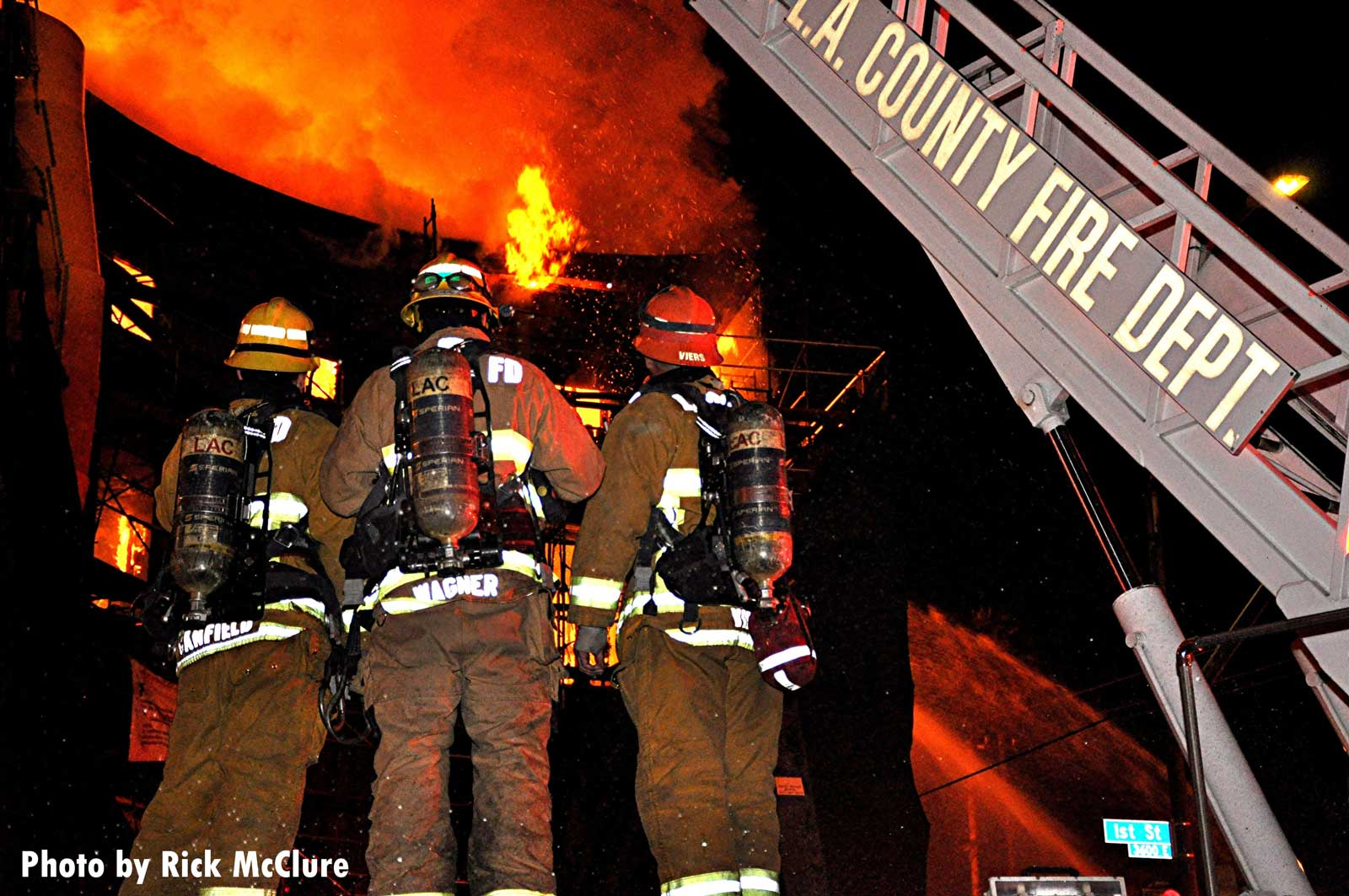 Firefighters observe the flames
