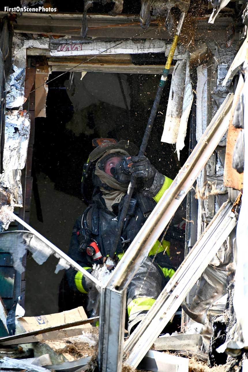 Firefighter performs overhaul at Queens fire