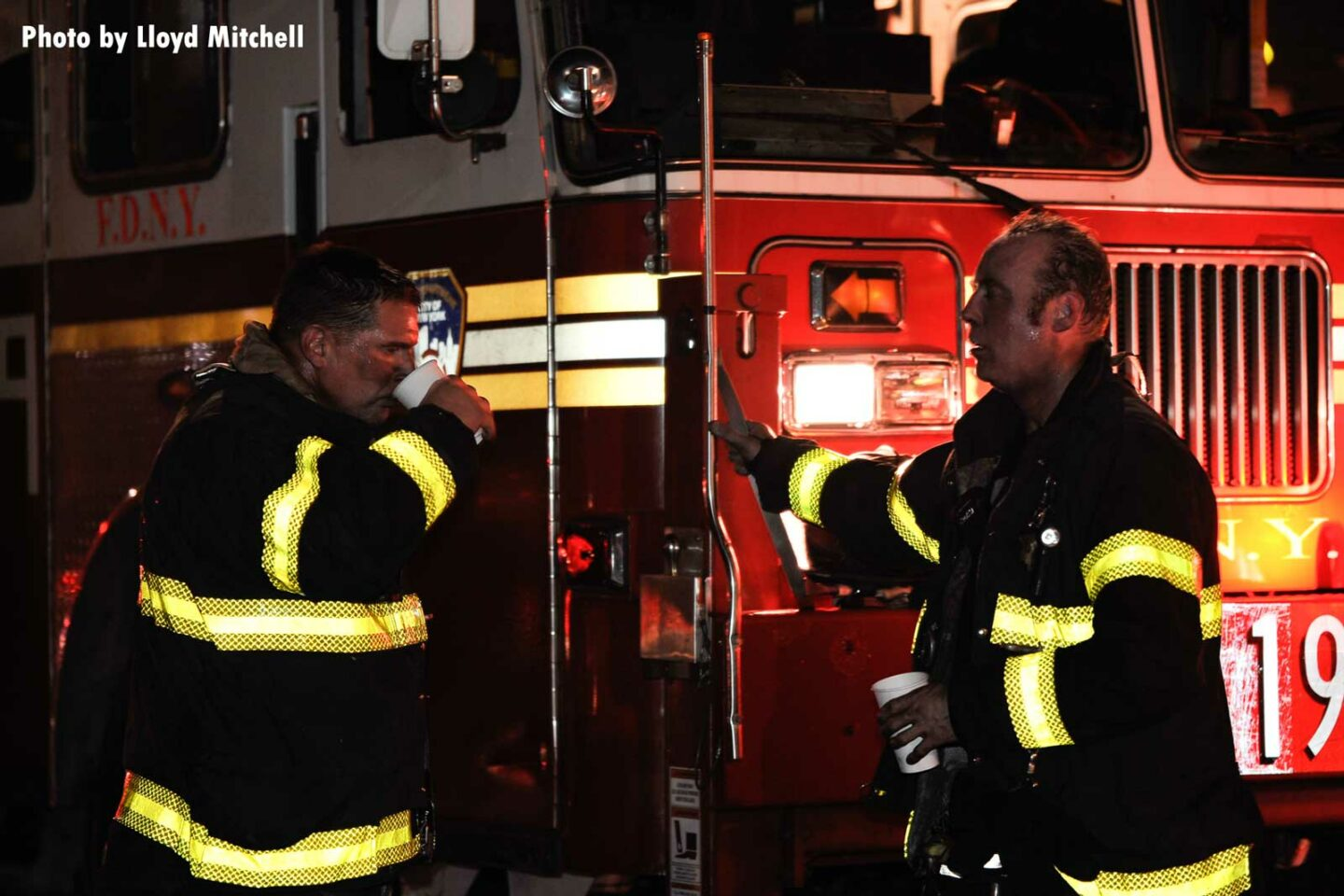 FDNY firefighters converse at the scene of a fire