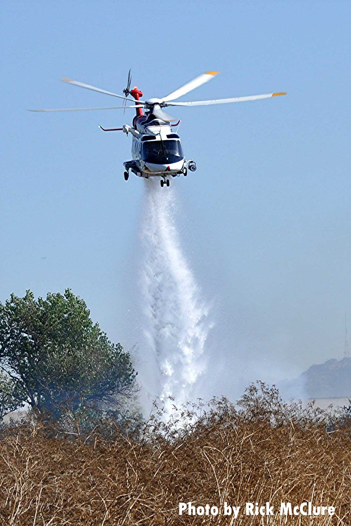 Helicopter making a drop on vegetation fire in Los Angeles
