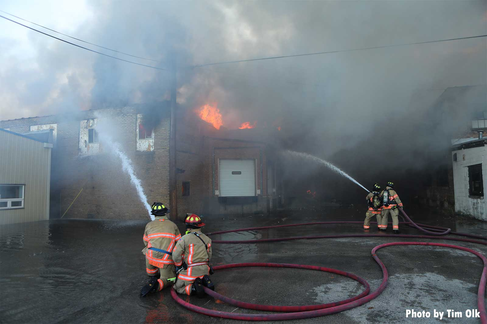 Two pairs of firefighters with hose streams on building