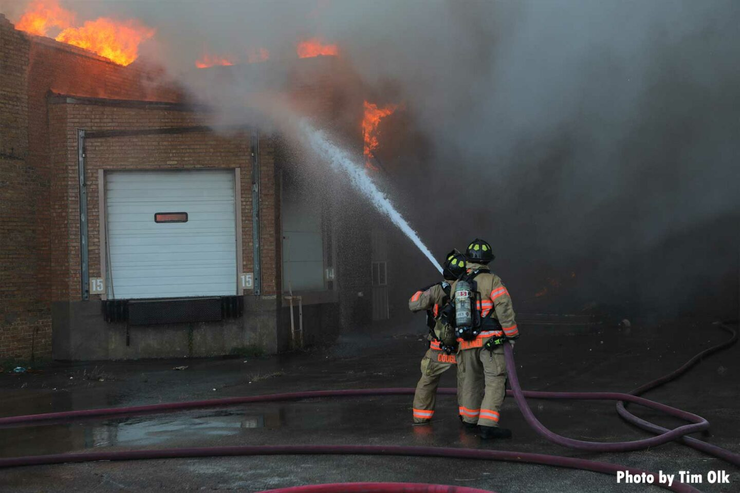 Firefighters use hoseline on exterior of the building