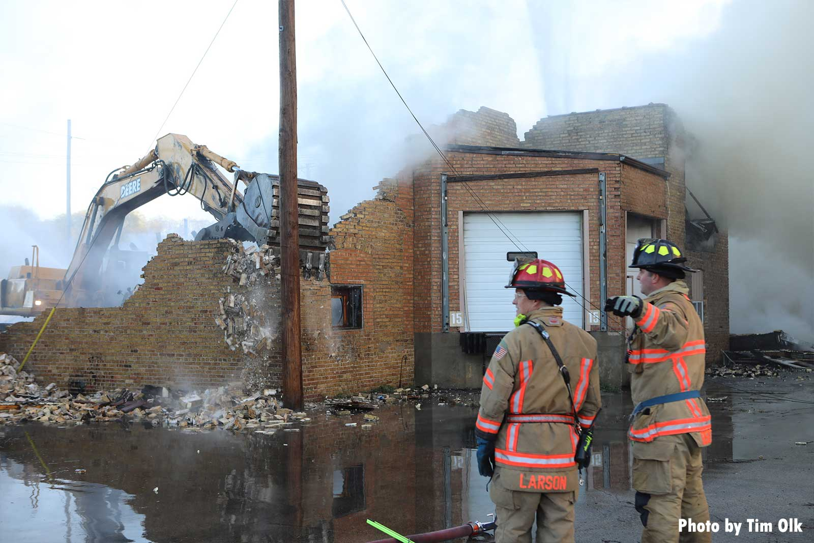 Firefighters with excavator in background knocking down building