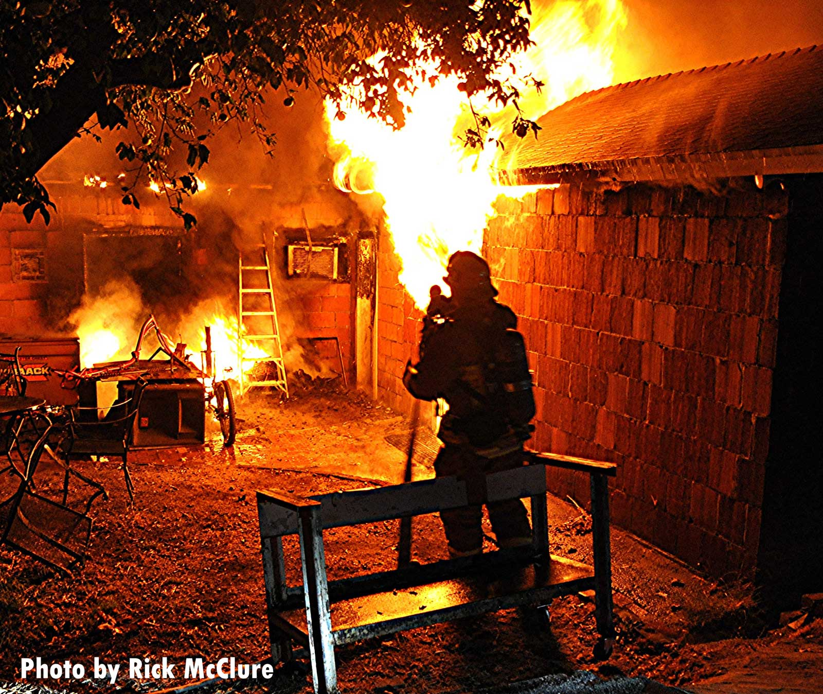 Firefighter silhouette against flames raging inside a home