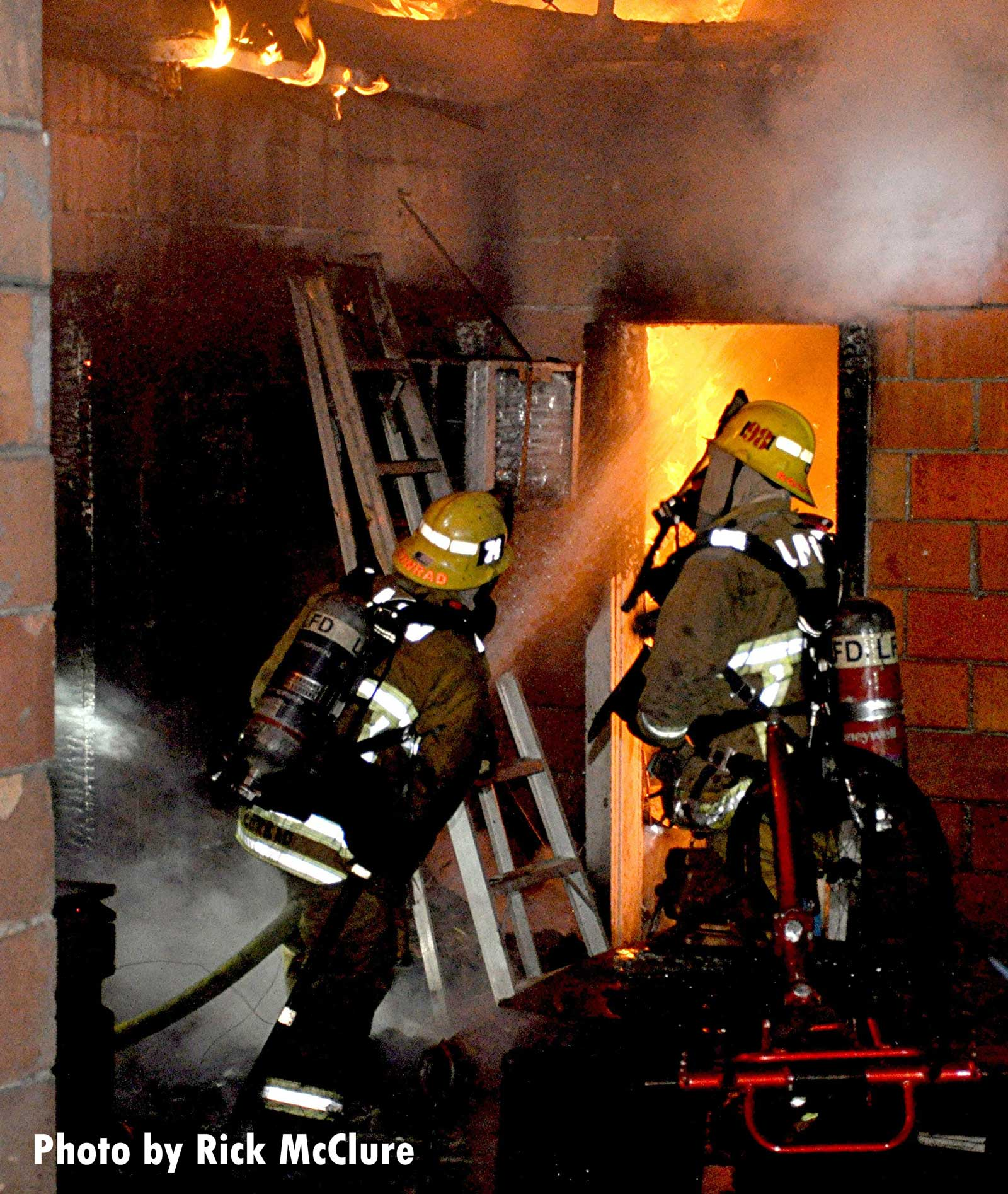 A firefighter blasts water through a doorway on flames