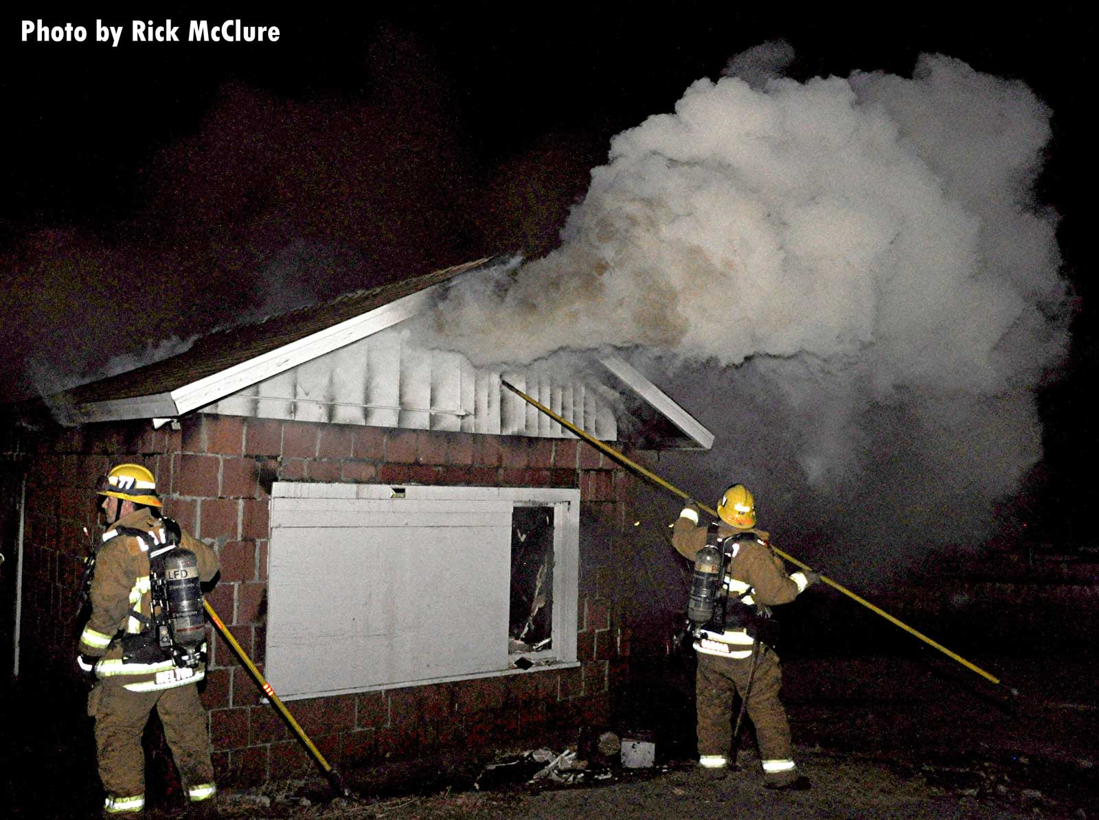 A firefighter uses a hook to open up on the outside of a building as smoke pumps out of the structure