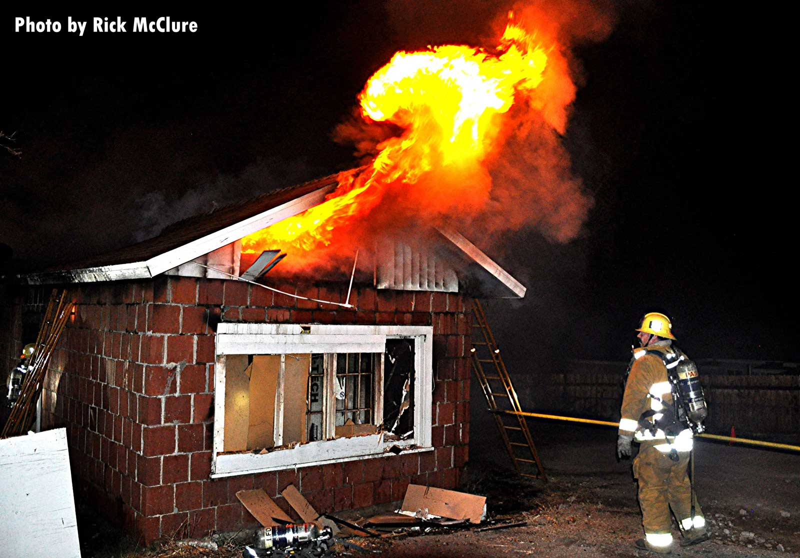 A firefighter with a hook and flames venting from the building