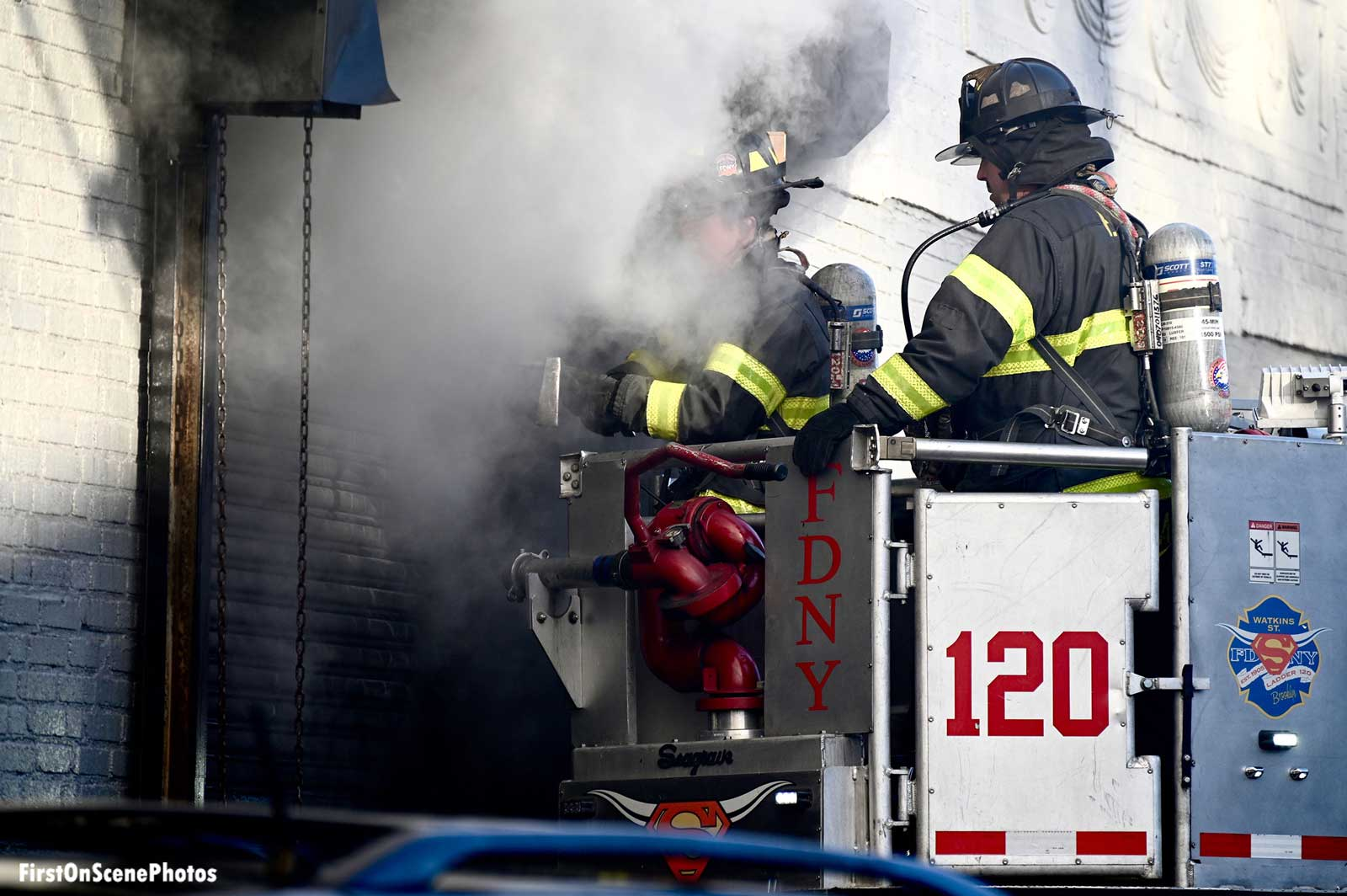 FDNY firefighters in a bucket with smoke