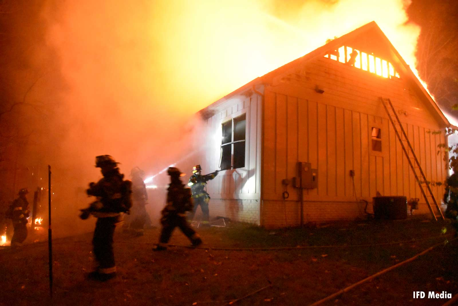 Firefighters at work at flames course through building