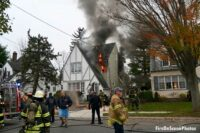 Flames shoot from the second floor of a home as firefirefighters work