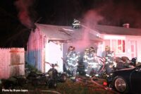 Firefighters working at the scene of a house fire on Long Island