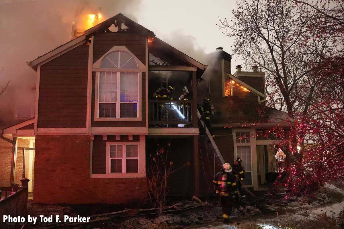 Firefighters stretch lines on apartment fire