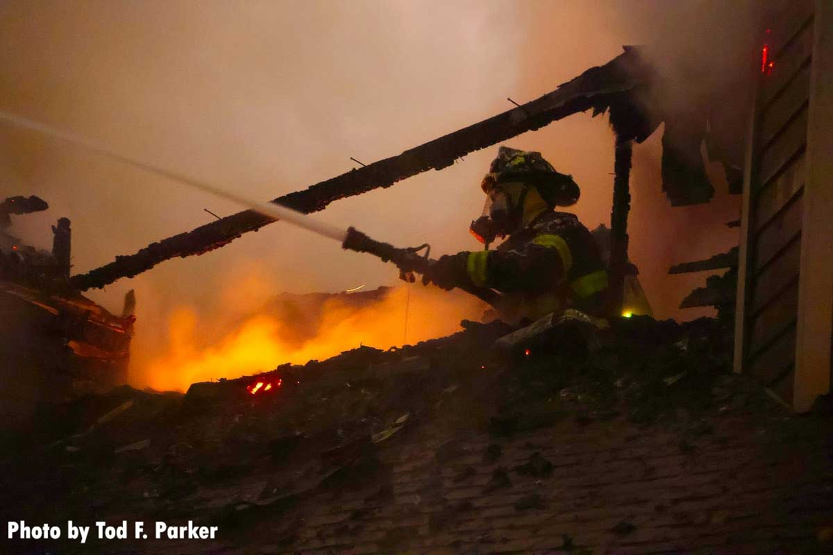 A firefighter pouring water on the flames