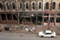 In this Dec. 29, 2020 file photo, debris remains on the sidewalk in front of buildings damaged in a Christmas Day explosion in Nashville, Tenn. The Christmas Day bombing in downtown Nashville led to communications outages over hundreds of miles in the southern U.S., raising concerns about the vulnerability of U.S. networks. Widespread service outages followed the explosion, which damaged a major AT&T network hub, extended hundreds of miles to at least four neighboring states, disrupting 911 call centers, hospitals and flights out of the Nashville airport.