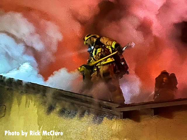 A firefighter on the roof at a Los Angeles house fire