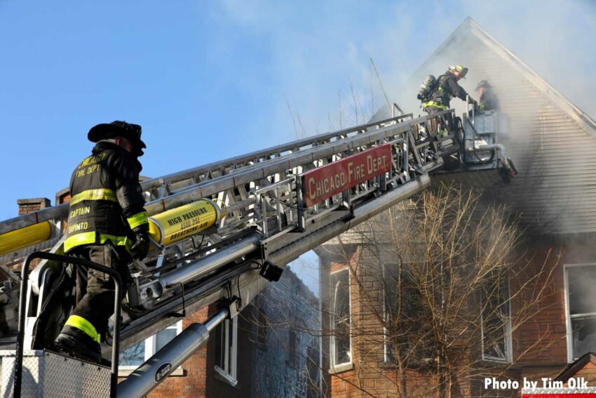 Chicago Fire Department tower ladder with members operating at house fire