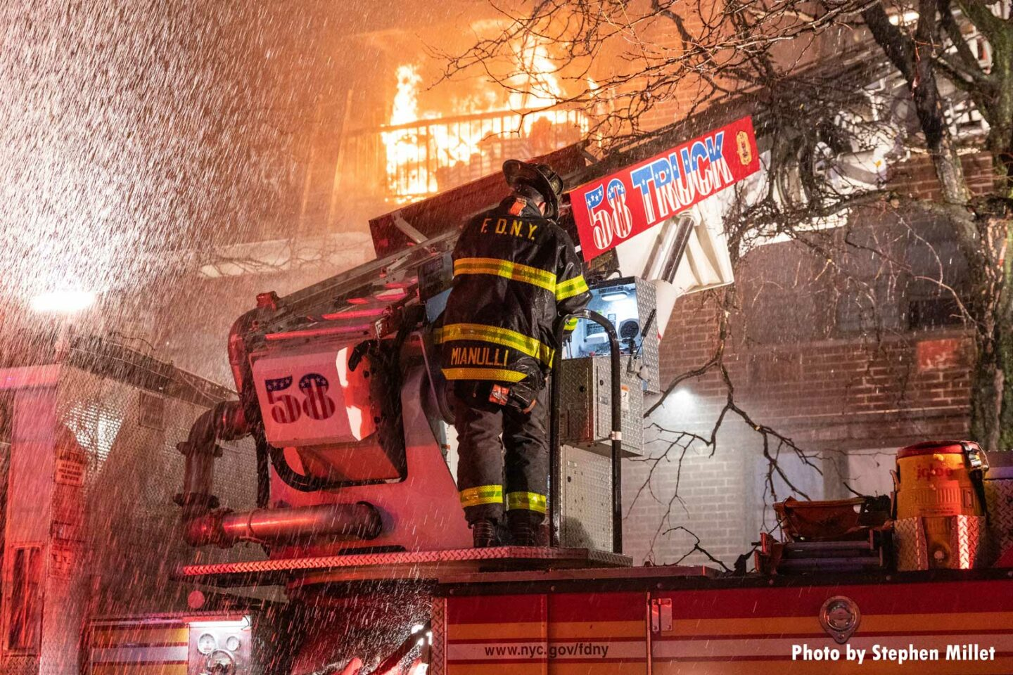 Flames rage in a building as a firefighter on 58 Truck works. This Bronx fire was the first multiple-alarm of 2021 for the FDNY