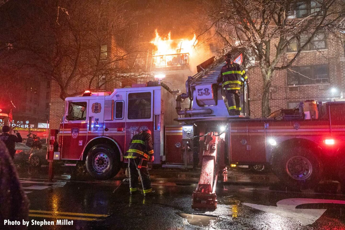 Flames raging from a multiple dwelling in the Bronx as FDNY members work