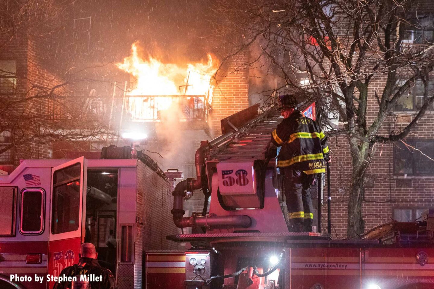 Flames rage behind a firefighter working on Truck 58 in the Bronx