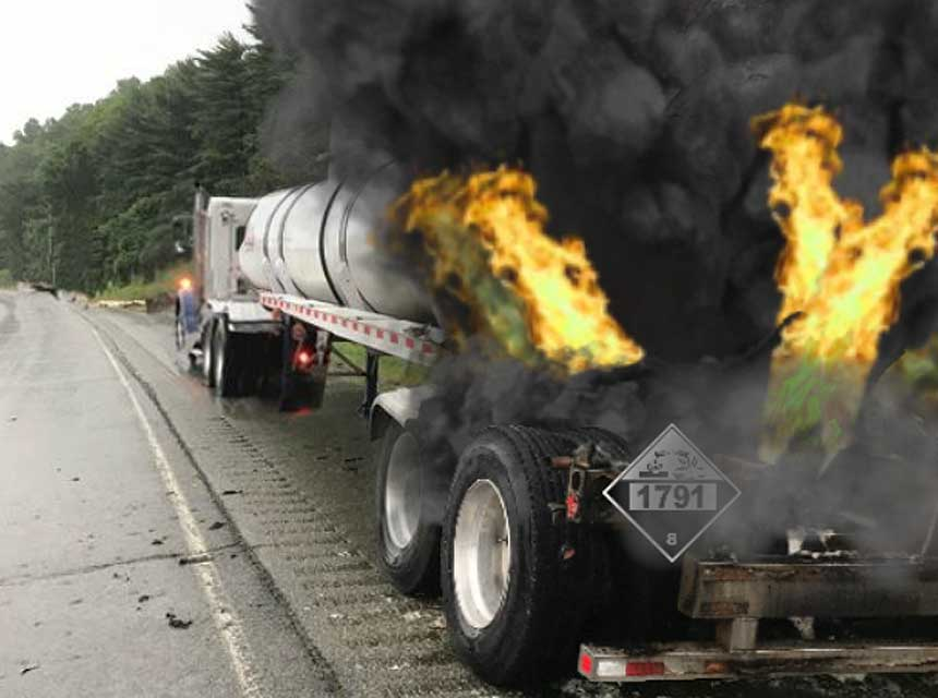 Flames shooting out the back of hazmat-placarded tanker truck on roadway