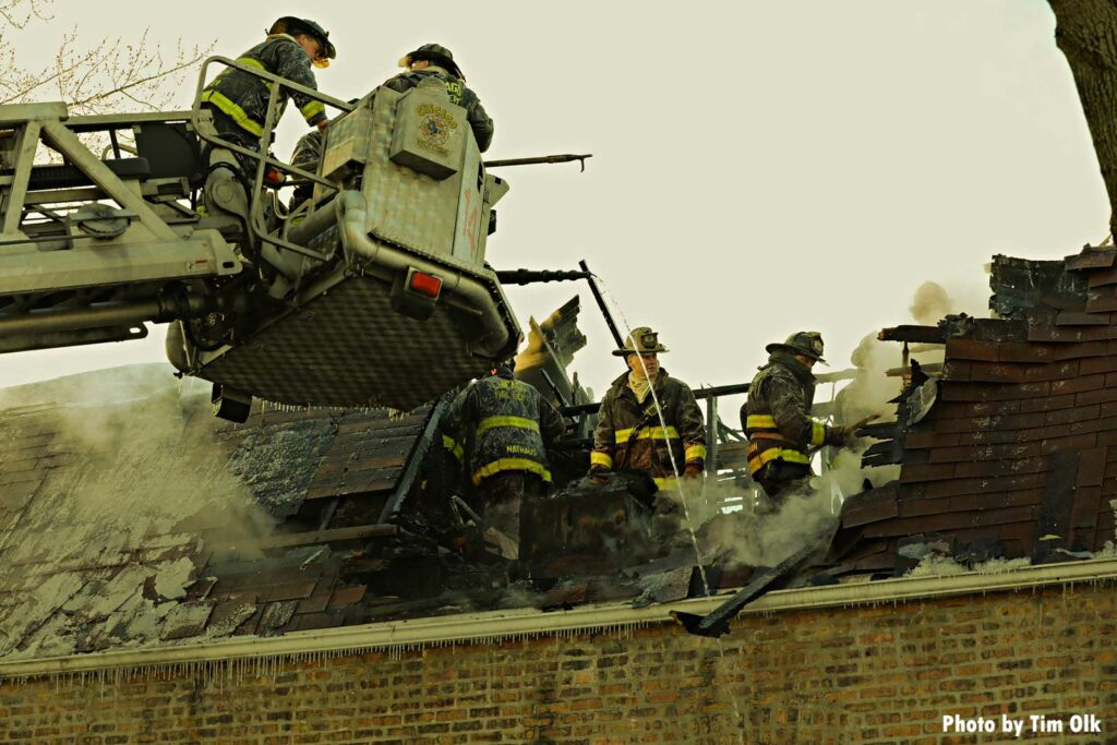 Chicago firefighters in a bucket while others perform overhaul at structure fire