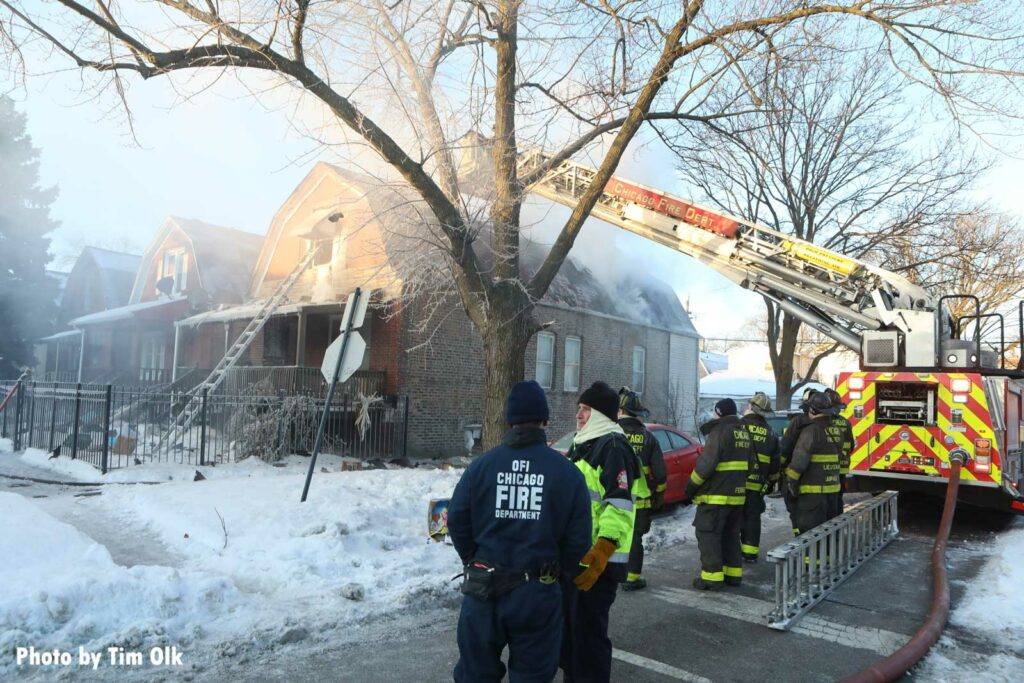 Chicago fire crews at the scene of a house fire with Chicago tower ladder extended