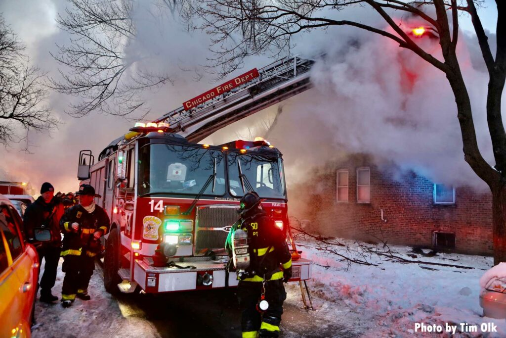 Chicago firefighters and tower 14 at house fire with flames and smoke showing