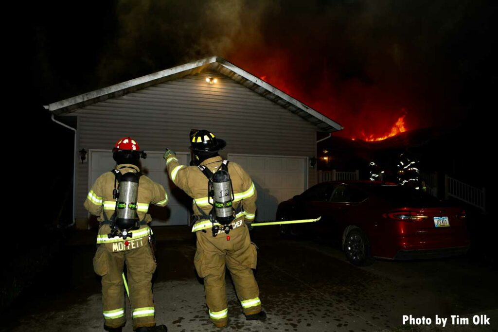 Two firefighters, one with a hook, at house fire