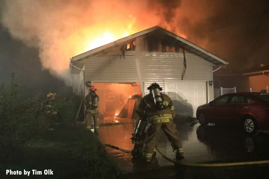 Firefighters put water onto garage area as flames burn through roof of home