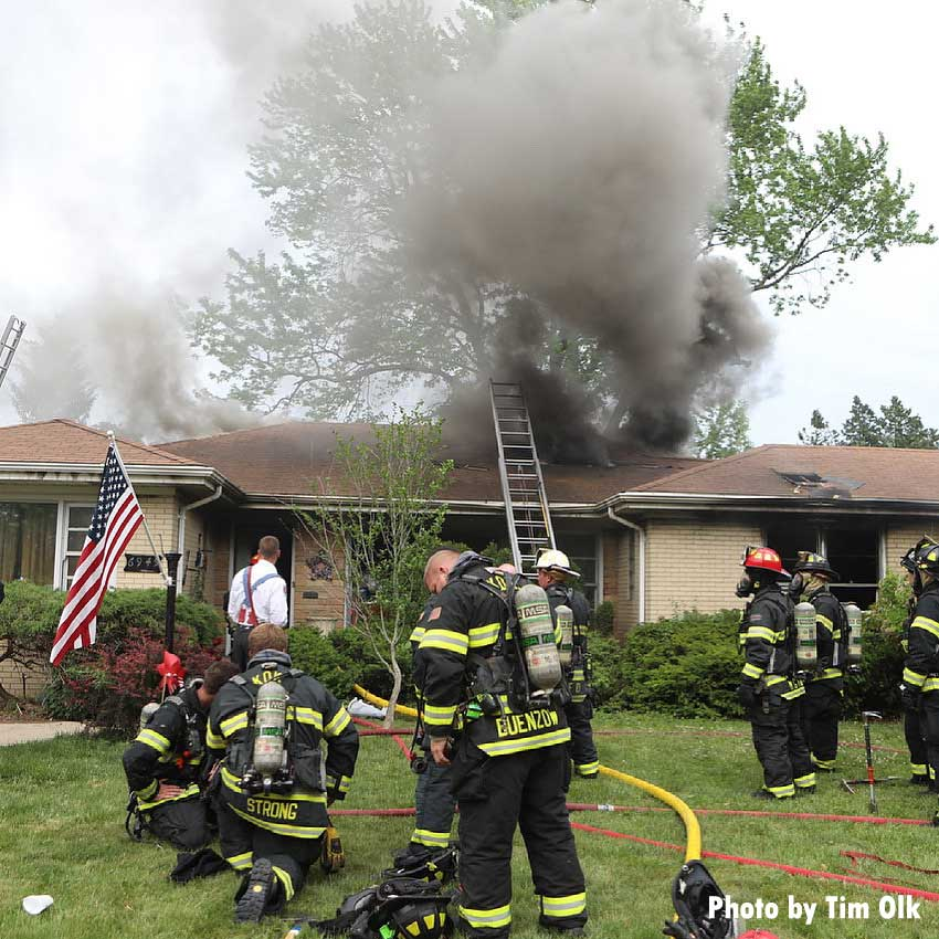 Firefighters mask up in yard as smoke vents from roof at house fire