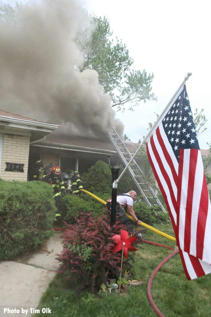 U.S. Flag with firefighters putting a hoseline into the interior of a burning home