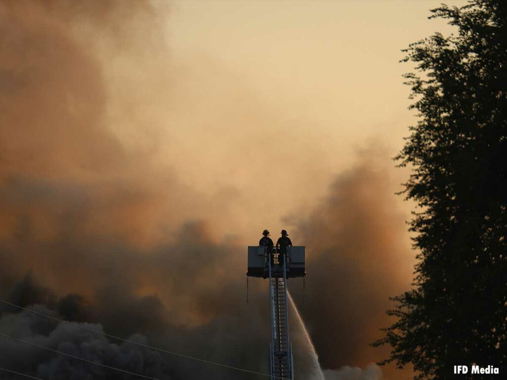 Two firefighters in a tower ladder bucket with an elevated stream