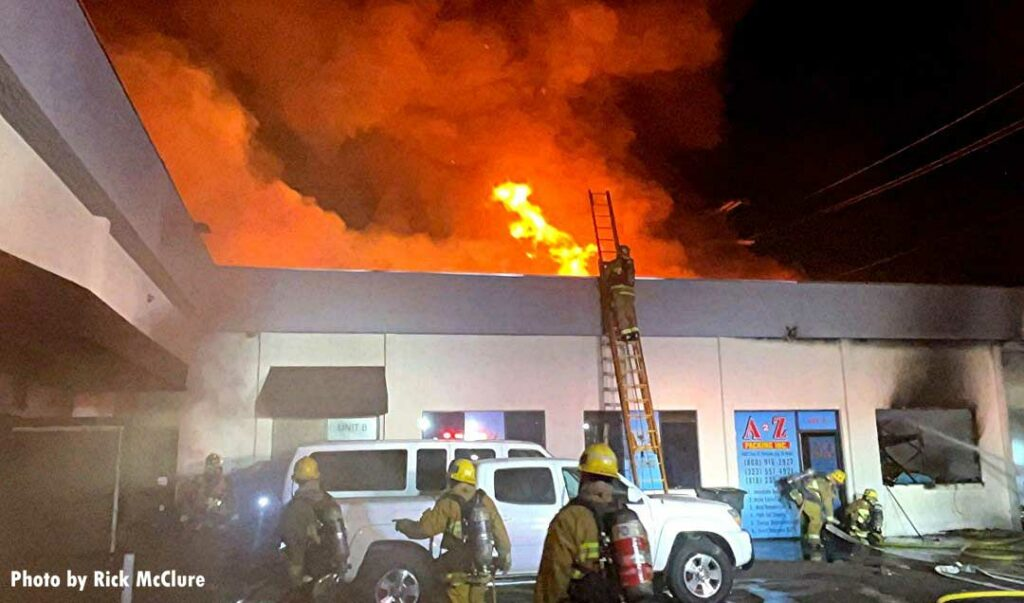 LAFD firefighter on a ladder with fire coming through the roof