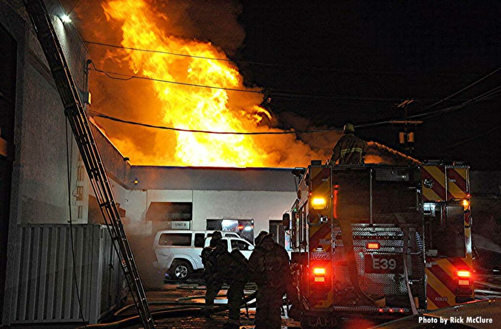 LAFD firefighters with major flames shooting through roof of fire building