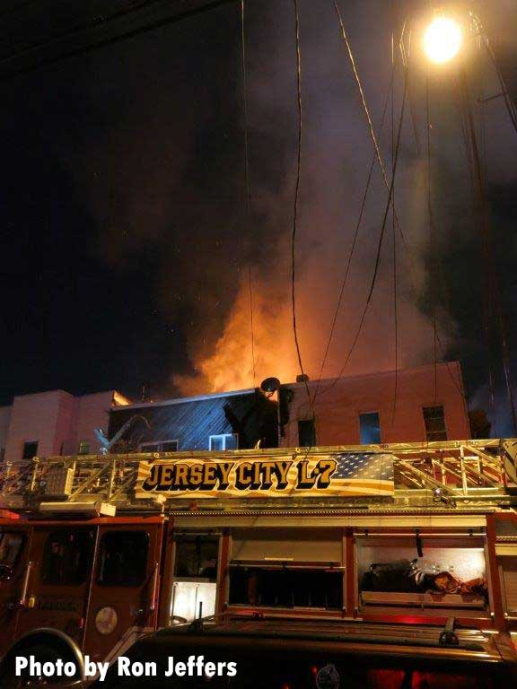 Jersey City Ladder 7 outside fire building with flames showing