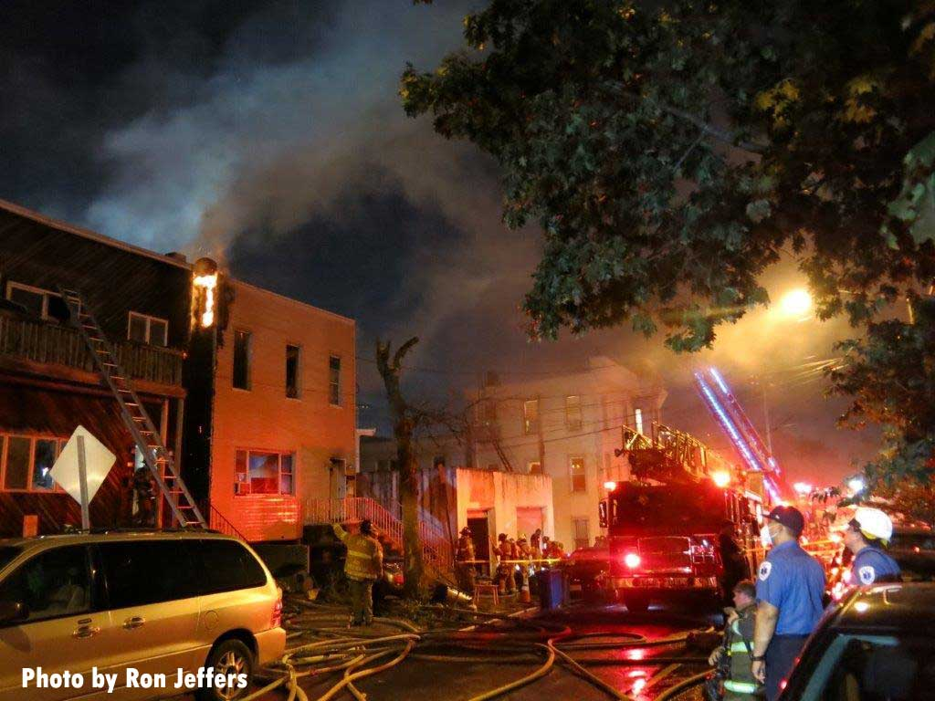 Flames tear along the top of a building in Jersey City