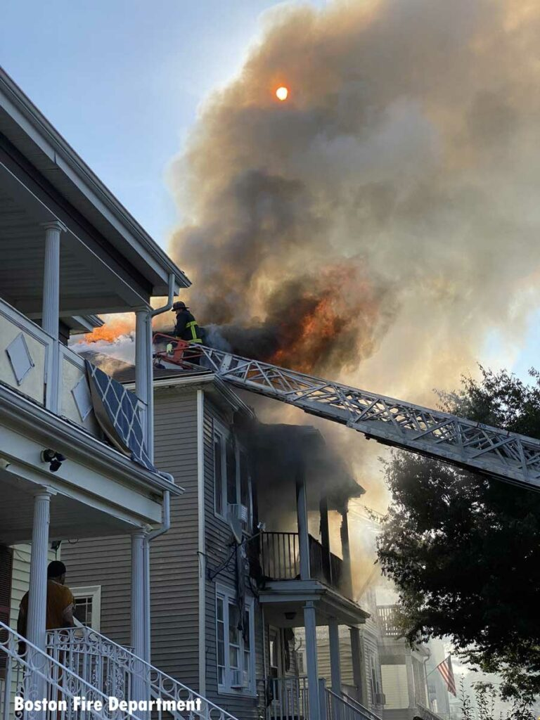 Boston firefighter on aerial flowing water at house fire
