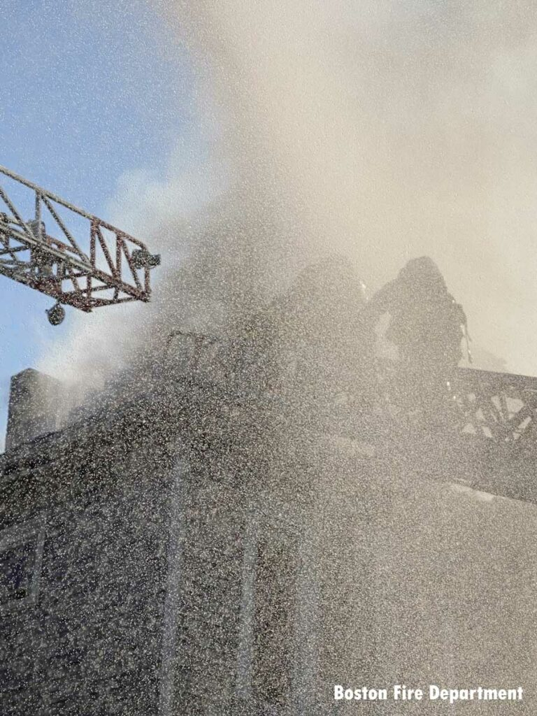 Spray from water conceals firefighters operating on aerials