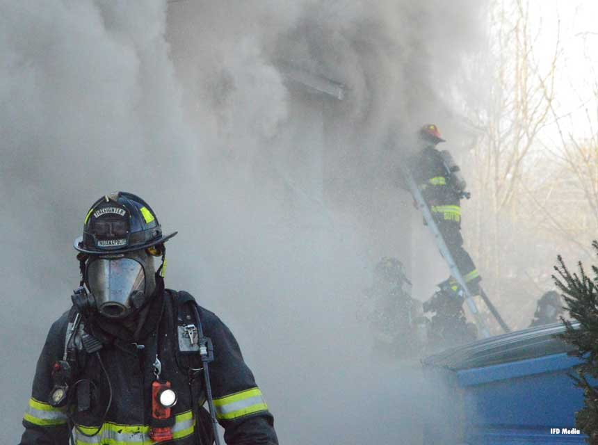 Indianapolis firefighter in full gear with firefighter on a ladder in the background partly obscured by smoke