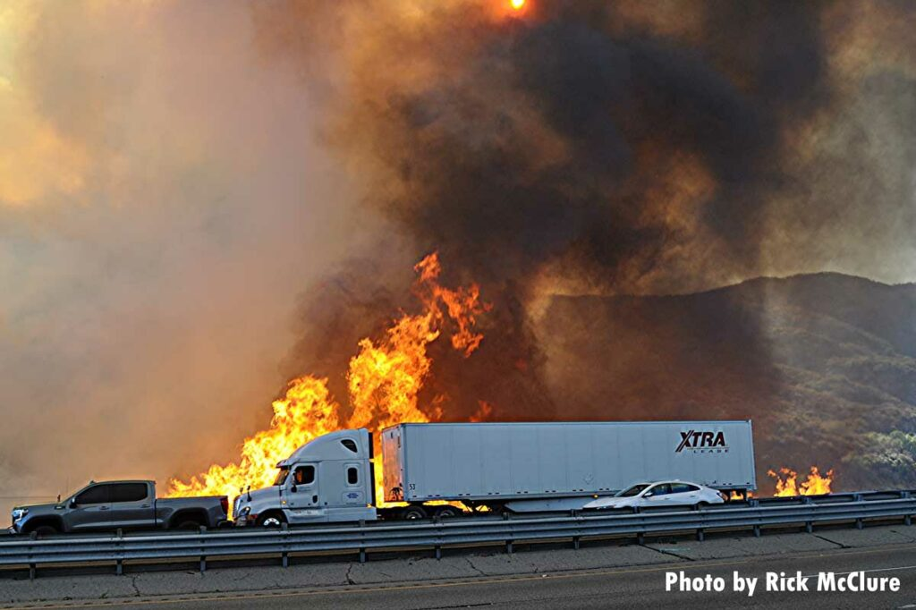 Tractor trailer drives past massive wildfire flames