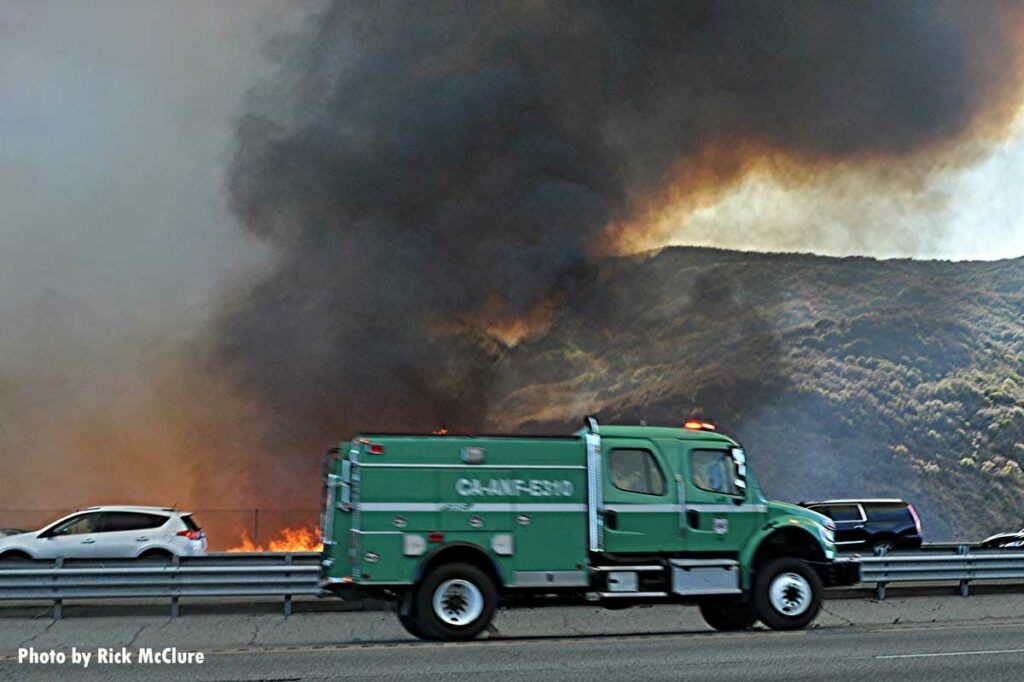 Fire burns on side of California roadway as traffic whizzes by