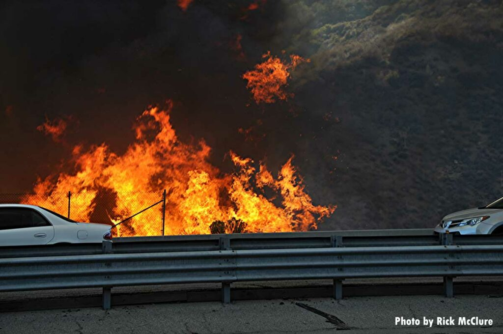 Cars drive past wildfire flames